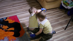 Twin kids boys have fun enjoy playing fighting with boxing gloves at home Stock Footage