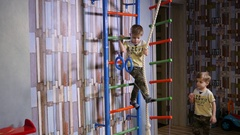Active twin kids boys have fun play at home sway hang and climb on wall bars Stock Footage
