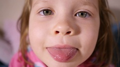 Little kid girl face portrait   grimace and show tongue closeup slow motion Stock Footage