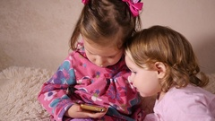 Little kids girlds sisters sit at home watching a smart phone cartoons Stock Footage