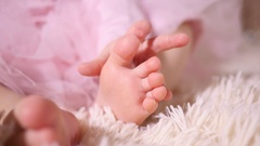 Little baby toddler fingers touching strocking her leg foot toes closeup slow Stock Footage