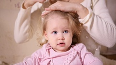 Maternal care, mother tenderly comb hair make hairstyle of her little baby girl Stock Footage