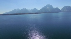 Peaceful shot of Jackson Lake with mountains in the horizon as the camera Stock Footage
