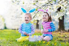 Easter egg hunt. Kids with bunny ears in spring garden. Stock Photos