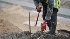 Slowmotion worker in red gloves hammering iron rod in ground with sledgehammer Stock Footage