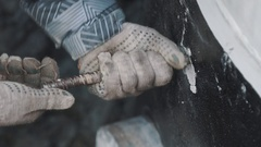Man in work gloves and striped jacket untwist piece of metal rod from concrete Stock Footage