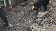 Workers tossing macadam with shovel and boots in ditch. Slowmotion Stock Footage