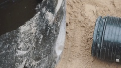 Sticking black ribbed plastic pipe in to round hole in concrete in sand ditch Stock Footage