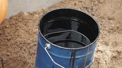 Roll dipping in blue bucket with black tar or paint on sand surface Stock Footage