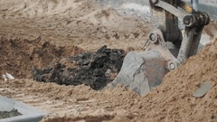 Excavator bucket digging soil sand and dirt hole at building site. Slowmotion Stock Footage