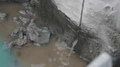 Dirty water pouring through slit in concrete to puddle Stock Footage