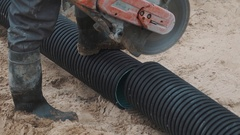 Warker nagging ribbed plastic pipe with circular saw on sand surface, slowmotion Stock Footage