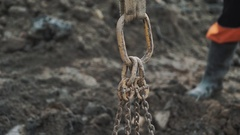 Metal noose holding on band with few chains attached at dirty building site Stock Footage