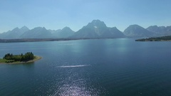Camera flies backwards over Jackson Lake with a mountain range on the horizon Stock Footage