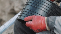 Man in red rubber glove cutting piece of black ribbed plastic pipe with knife Stock Footage