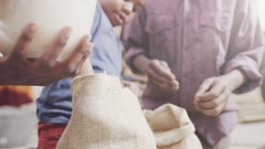 4K Family from poor African community work together measuring rice or grain. Stock Footage