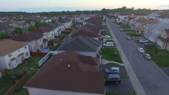 Camera flies over houses in a suburb in the late summer evening Stock Footage