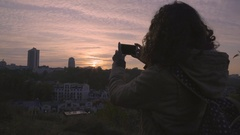 Inspired female student filming cityscape with amazing sunset on smartphone Stock Footage