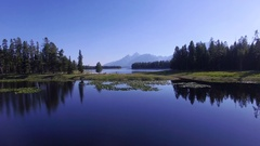 Camera flies over a calm Jackson Lake with mountains along the horizon Stock Footage
