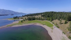 A forest is revealed as the camera ascends above a shoreline on Jackson Lake Stock Footage
