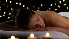 Girl resting in room with burning candles and dark background Stock Footage