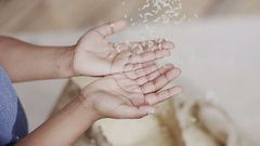 4K Rice being poured into the hands of a small child from poor African community Stock Footage