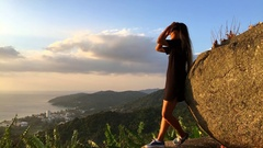 Young Tourist Girl Watching Amazing Sunset at the Viewpoint. Slow motion travel Stock Footage