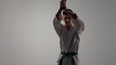 Downward katana strikes are shown by a 18 year old sportswan in studio Stock Footage