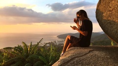 Gorgeous Woman Sitting at the Cliff and Texting on Smartphone gadget. Phuket Stock Footage