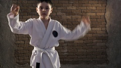 A seven year old Caucasian boy trains a complicated karate sequence in studio Stock Footage