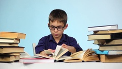 Little boy reading a different book. Blue background. Slow motion Stock Footage