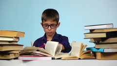 Little boy writes in a notebook, and he does not like. Blue background. Slow Stock Footage