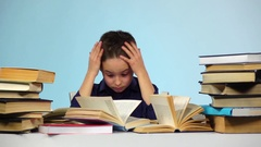 Boy wears glasses and leafing through the book. Blue background. Slow motion Stock Footage