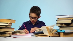 Little boy pulls out sheets of books. Blue background. Slow motion Stock Footage