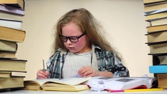 Girl sits at a table with books and nervous. Blue background. Slow motion Stock Footage
