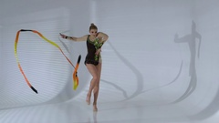 Rhythmic gymnast gracefully dancing with a ribbon in his hands. White background Stock Footage