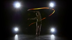 Gymnast with the ribbon in his hands doing acrobatic moves. Black background Stock Footage