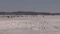 People out on frozen lake in the sun enjoying ice fishing and nice weather Stock Footage