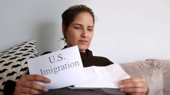 Woman sitting on couch reading USA immigration papers Stock Footage