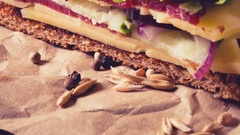 Two pieces of sandwich on old papper with big cutting board. In Stock Footage