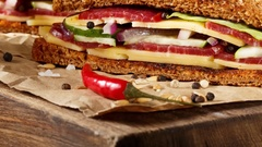Two pieces of club sandwich on old papper with big cutting board Stock Footage