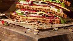 One piece of sandwich on old papper with big cutting board. In v Stock Footage