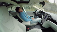 Male driver sleeping behind the wheel in self-driving autonomous electric car Stock Footage