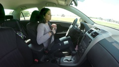 Young Woman Fastens Her Seat Belt And Starts Her Car Stock Footage
