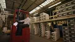 4K Forklift truck driver in a coffee factory moving and loading goods Stock Footage