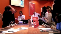 People asking sales clerk about cellphone plan at wind store Stock Footage