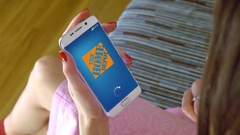 Young woman holding a cell phone with loading The Home Depot mobile app Stock Footage