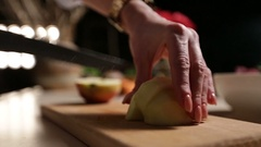 Female hand slicing peeled apple on cutting board Stock Footage
