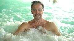 Mature man enjoying hot tub bath in spa center Arkistovideo