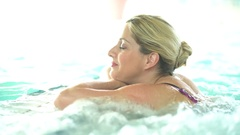 Beautiful blond woman relaxing in thalassotherapy thermal water Stock Footage